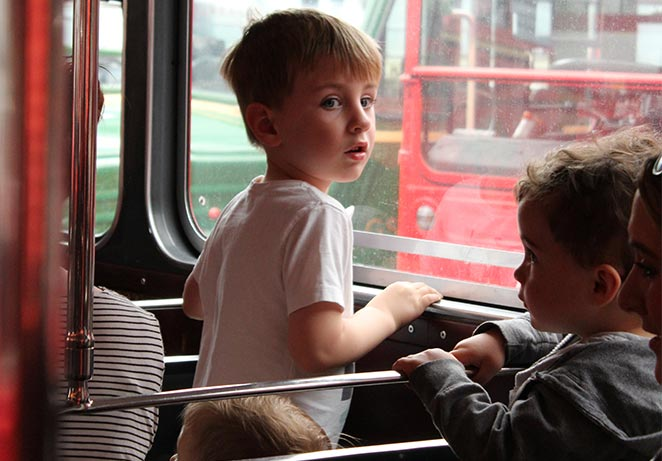 Young boy looking out of a bus window
