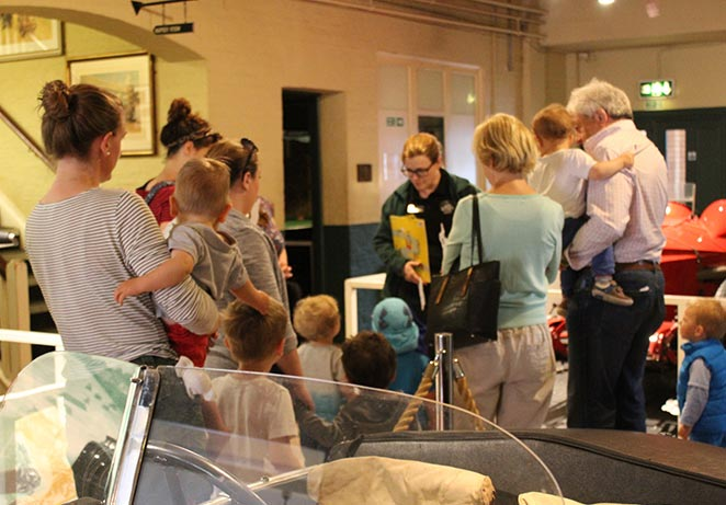 Group of adults and under 5s exploring the cars on display inside the museum.