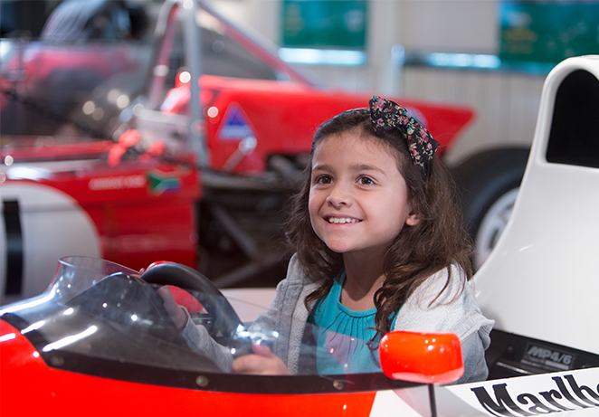 Girl sitting in F1 car family visit.jpg